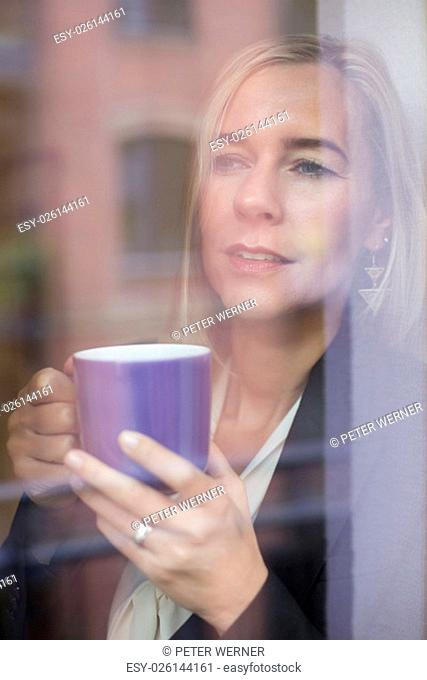 woman holding a cup and looking out of a window