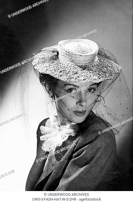 United States: c. 1948 A fashion photo of a woman wearing a hat with a veil