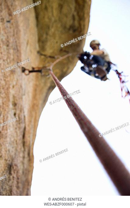 Detail of a rope with an unfocused climber climbing in the background