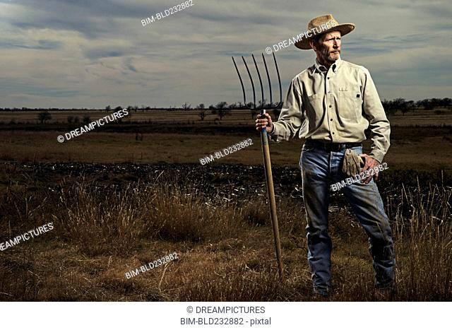 Farmer standing with pitchfork in field