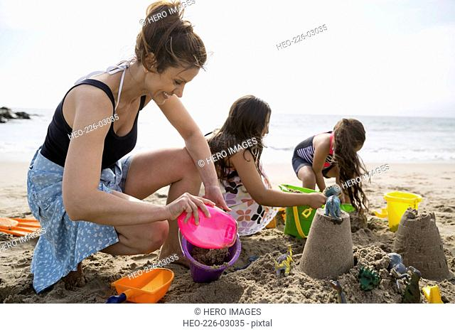 Family making sandcastles on sunny beach