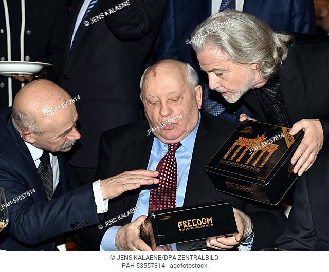 Former Soviet President Michail Gorbachev (C) receives a limited edition box of biscuits entitled 'Freedom' from Hermann Buehlbecker (R)