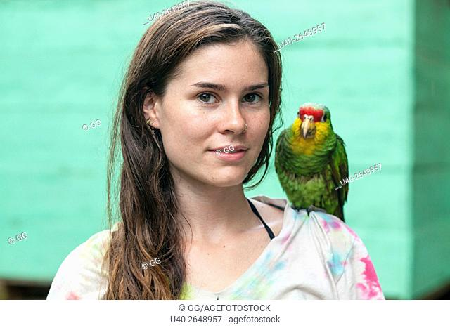 Guatemala, Rio Dulce, young woman with parrot