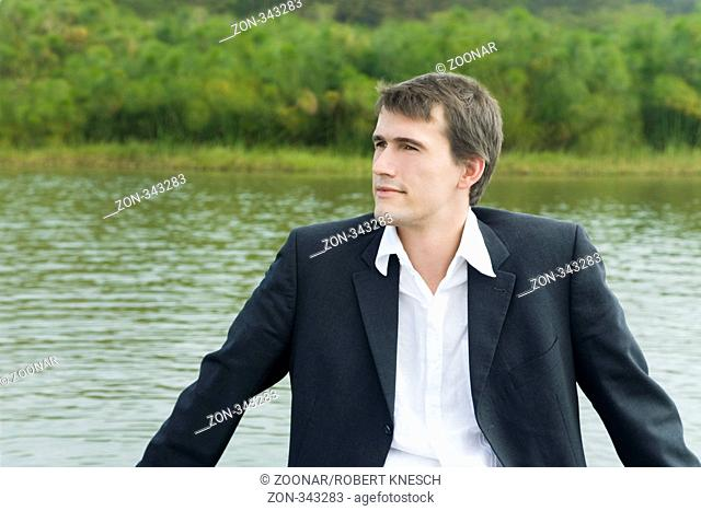 Junger Manager sitzt alleine in einem Boot auf einem See