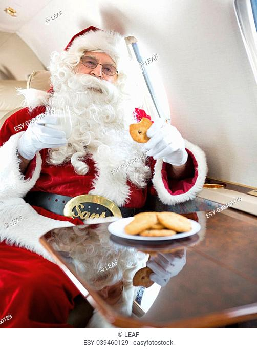 Man in Santa costume eating cookies while holding milk glass in private jet