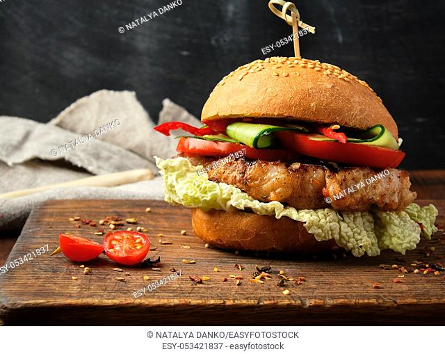 homemade hamburger with pork fried steak, red tomatoes, fresh round bun with sesame seeds on a vintage brown wooden board