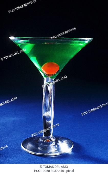 A sour apple martini on a blue background