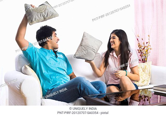 Brother and sister fighting with pillows