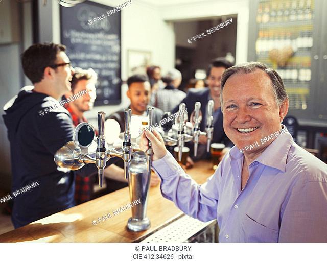 Portrait smiling male bartender standing at tap behind bar