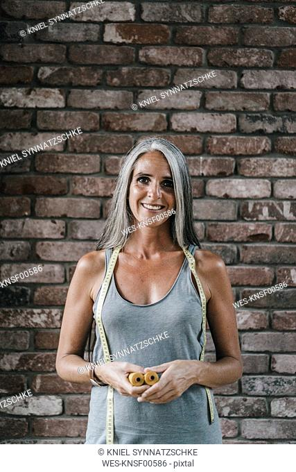 Portrait of woman in front of brick wall holding cotton reels