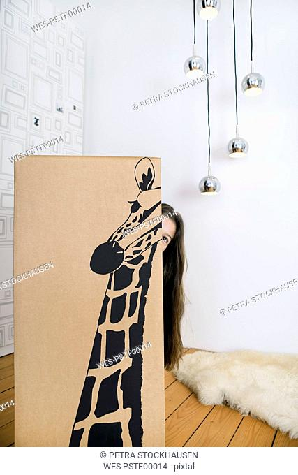 Girl inside a cardboard box painted with a giraffe