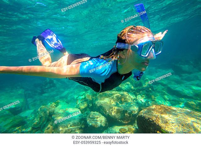 Close up of female apnea swims in tropical turquoise sea of Racha Noi, Phuket in Thailand