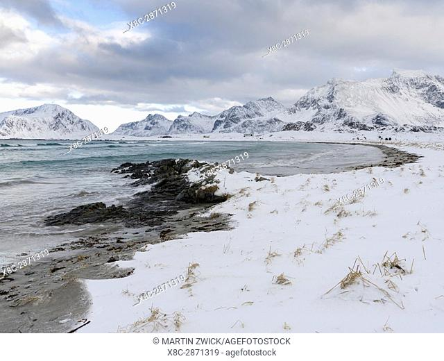Ytresand Beach near village Fredvang, view over to island Flakstadoya. The island Moseknesoya, the Lofoten islands in northern Norway during winter