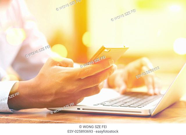 Asian Indian businessman using smartphone and laptop computer at outdoor cafeteria, golden sunset background