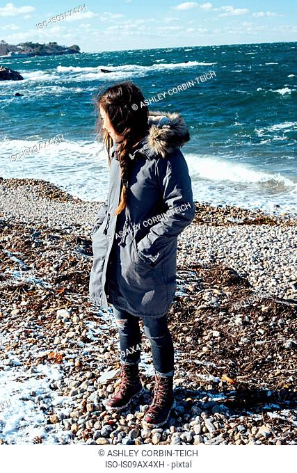 Full length view of woman on shingle beach wearing winter coat looking away