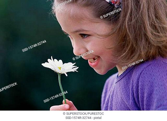 Side profile of a girl holding a flower