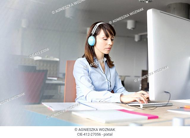 Brunette businesswoman with headphones working at computer in office