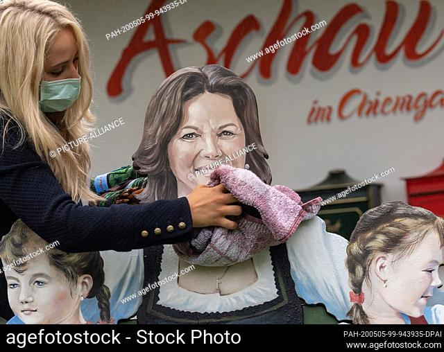 05 May 2020, Bavaria, Aschau Im Chiemgau: Stefanie Sattlberger, a businesswoman for tourism and leisure, wipes the newly painted portrait of Ilse Aigner (CSU)