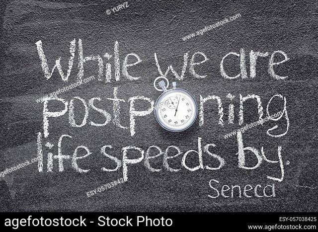 while we are postponing life speeds by - quote of ancient Roman philosopher Seneca written on chalkboard with vintage stopwatch instead of O