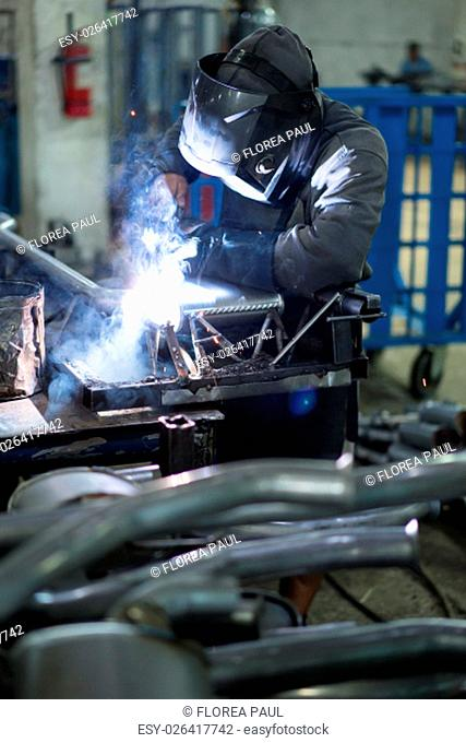 left side dynamic view of a worker wearing protective gear, with mask, leather apron and gloves, welding together pieces of an exhaust pipe