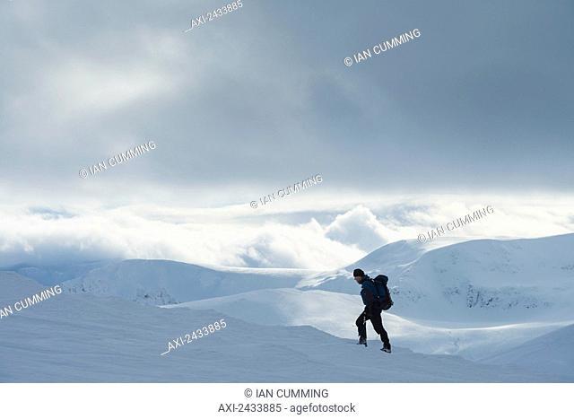 Walker on snowy, winter walk ascending Geal Charn, near Laggan; Scotland