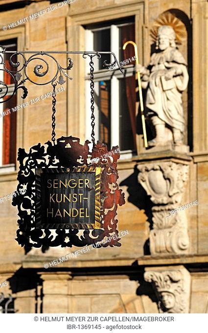 Decorative hanging sign of the art store Senger, in the back the figure of a saint on a façade, Karolinenstrasse, Bamberg, Upper Franconia, Bavaria, Germany
