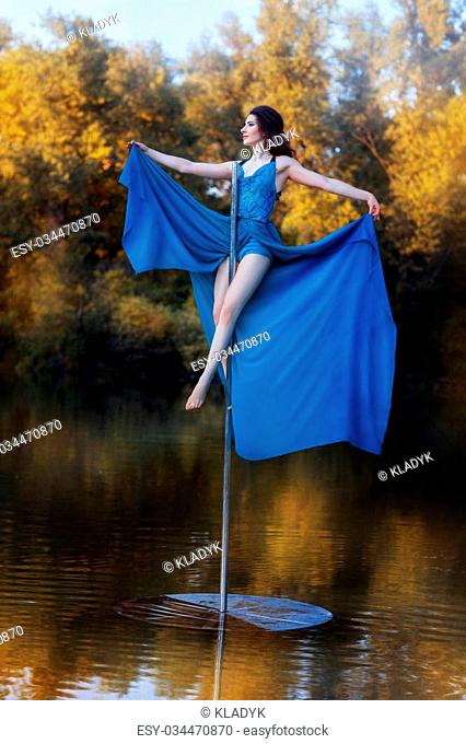 Girl in a blue dress sits high on a pole dance. See more photos of this series