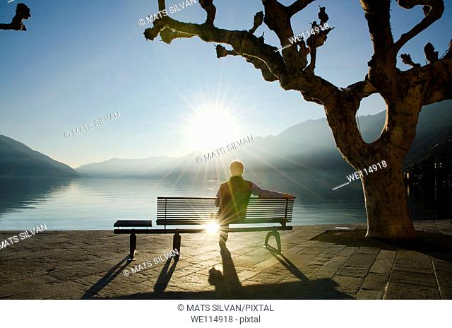 Man sitting on a bench and watching a sunset on alpine lake Maggiore with mountain in Ascona, Switzerland