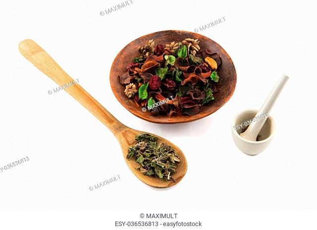 dried herbs in a wooden spoon, bowl and mortar