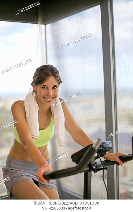 Pretty young woman doing spinning bike in fitness center and smiling at camera