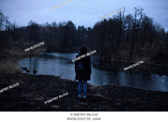 Caucasian woman standing near river at night