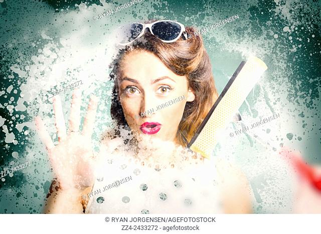 Funny retro pin-up housewife soaping up bathroom glass wall with foam when window cleaning with a squeegee. Fun fifties housewives