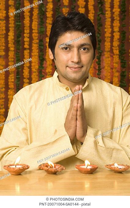 Portrait of a mid adult man praying on diwali