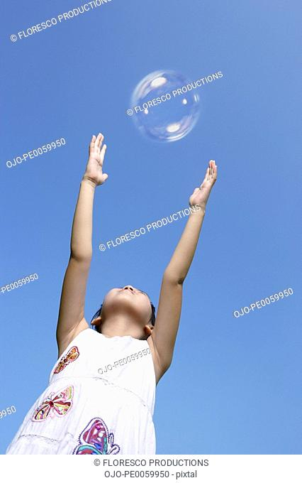 Young girl outdoors trying to touch a bubble