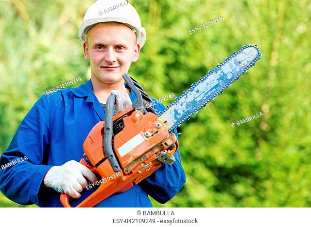 Lumberjack worker with chainsaw in work wear on forest background