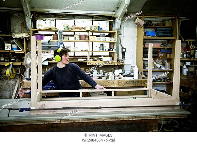 A woman working in a furniture maker's workshop, assembling a table