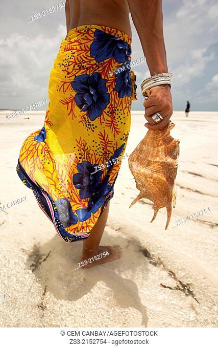 Woman holding a sea shell in the sea, Jambiani, Zanzibar Island, Zanzibar Archipelago,Tanzania, East Africa