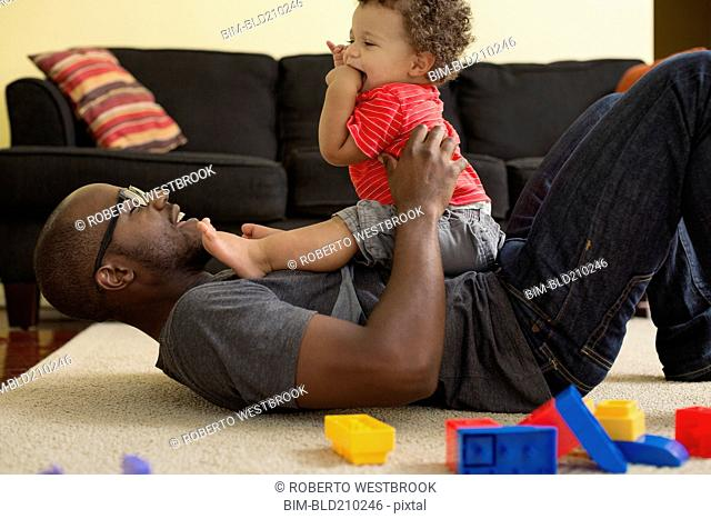 Father and toddler son playing in living room