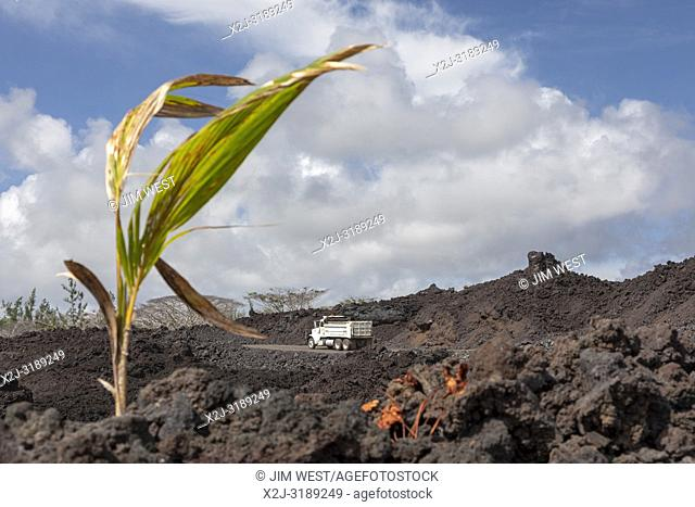 Pahoa, Hawaii - Trucks traverse a road being built on cooled lava from the 2018 eruption of the Kilauea volcano. This lava flow destroyed over 700 homes in the...