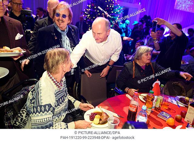 20 December 2019, Berlin: Musicians Frank Zander (l-r) and Dietmar Woidke (SPD), Minister President of Brandenburg, distribute Christmas goose to the guests at...
