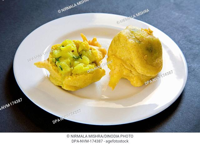 Indian fast food fried batata potato vada served in plate on black background 13-May-2010