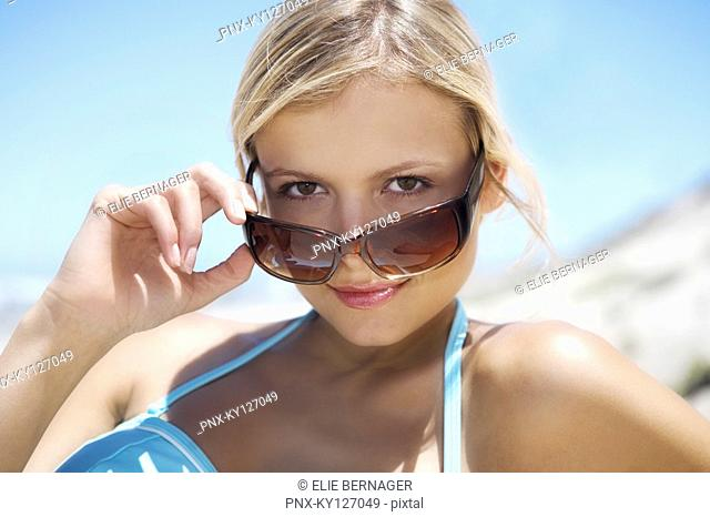 Portrait of a young woman looking over her sunglasses