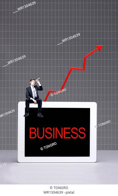 a business man sitting on a tablet with the word business