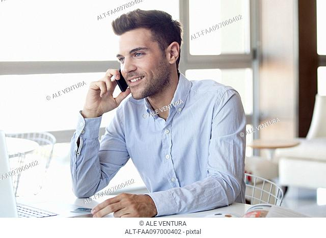 Man making cell phone call while using laptop computer