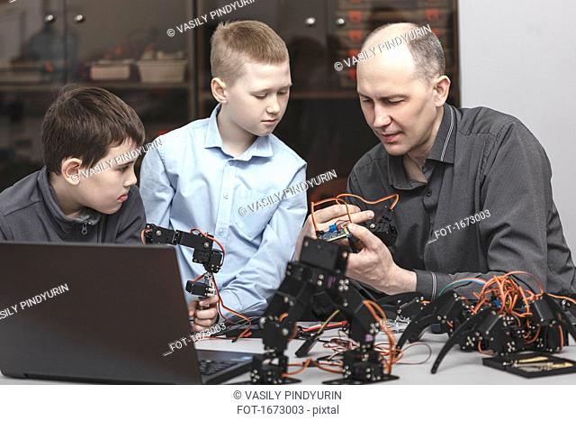Curious students looking at teacher operating machinery at table