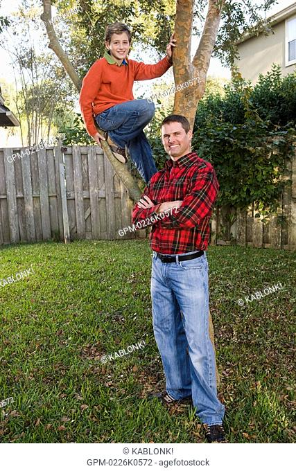 Portrait of happy father and son posing beside tree in backyard, looking at camera