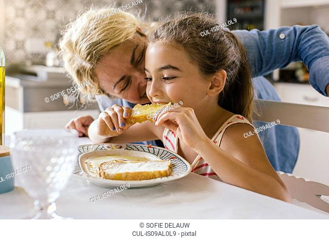 Girl eating toast with grandmother