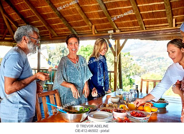 Happy friends enjoying healthy meal in hut during yoga retreat