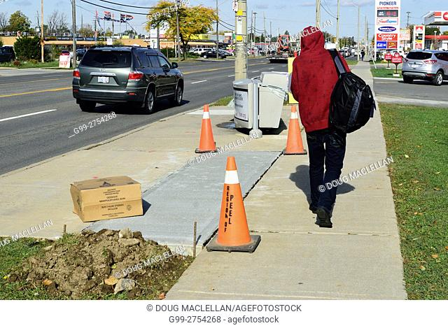 A man in a red hoodie walks past a cardboard box and orange pylons near a repaired sidewalk on Upper James Street in Hamilton, Ontario