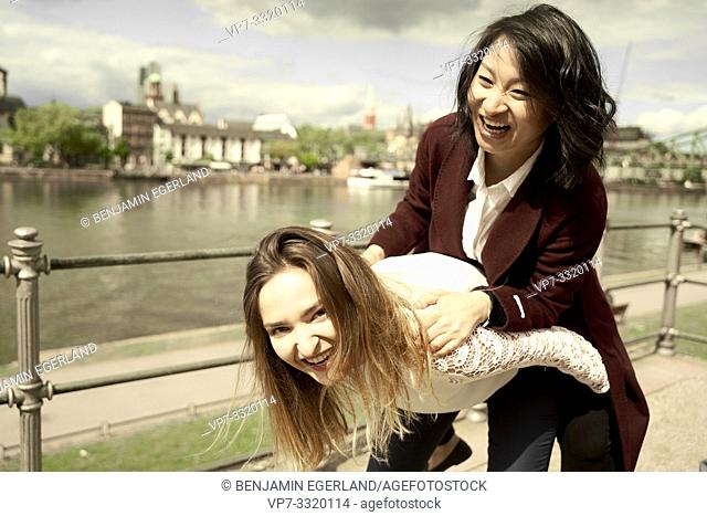 two funny friends piggyback outdoors at riverside of Main, in Frankfurt am Main, Germany